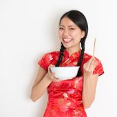 Portrait of Asian Chinese female eating, using chopsticks holding rice bowl, in traditional dress red cheongsam standing on plain background.