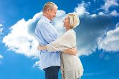 Happy mature couple hugging and smiling against cloudy sky
