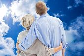 Mature couple hugging and looking against bright blue sky with clouds