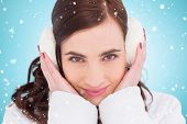 Pretty brunette with ear muffs against blue vignette