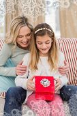 Daughter opening christmas gift with mother against snowflake frame