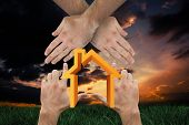 Hands making house shape against green grass under dark blue and orange sky