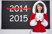 Smiling brunette in santa claus holding a piggy bank against black chalkboard
