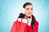 Brunette with ear muffs holding shopping bag full of gifts against blue vignette