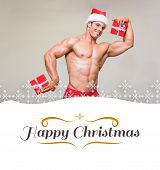 Shirtless macho man in santa hat holding gifts against border