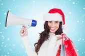 Smiling brunette holding gift bags and megaphone against blue vignette
