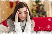 Brunette getting a headache on christmas day against fir tree forest and snowflakes