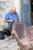 Old Fisherman Repairing Fishing Net