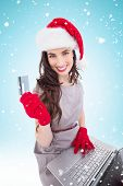 Beauty brunette shopping online with laptop against blue background with vignette