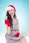 Smiling brunette shopping online with laptop against blue background with vignette