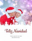festive mature couple holding gift against feliz navidad