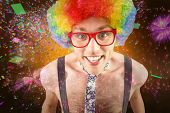 Geeky hipster in afro rainbow wig against colourful fireworks exploding on black background