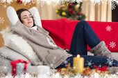 Brunette napping on the couch at christmas against fir tree forest and snowflakes