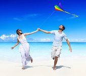 Couple flying a kite on the beach.