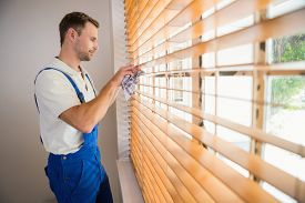 stock photo of handyman  - Handyman cleaning blinds with a towel in a new house - JPG
