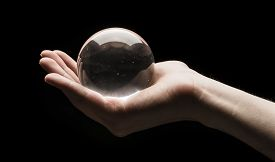 picture of divine  - Hand holding a clear transparent crystal glass ball in their palm isolated on black background - JPG