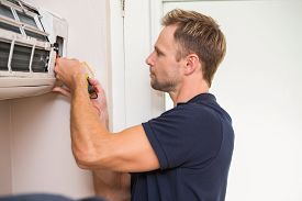 pic of handyman  - Focused handyman testing air conditioning on the wall - JPG