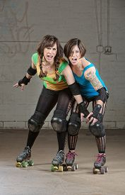 stock photo of roller-derby  - Aggressive women roller derby skaters threatening with a pose - JPG