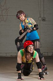 picture of roller-derby  - Hostile roller derby skater attacking woman with leg twist - JPG