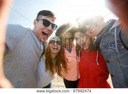 tourism, travel, people, leisure and technology concept - group of happy laughing teenage friends ta
