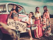 stock photo of hippy  - Multinational hippie hitchhikers with guitar and luggage on a road - JPG