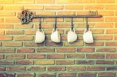 foto of hook  - Coffee cups hanging on hooks in front of brick wall  - JPG