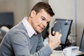 stock photo of frustrated  - Frustrated male customer service representative holding headphones in office - JPG