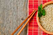 stock photo of chinese parsley  - Bowl with brown uncooked rice and leaf of parsley - JPG