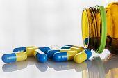 stock photo of penicillin  - Color medicine capsule spilling on a table - JPG