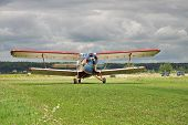 image of biplane  - Old propeller biplane taking off from the rough airstrip with stormy clouds on the background - JPG