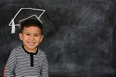 stock photo of schoolboys  - Happy little schoolboy posing in front of black chalkboard - JPG