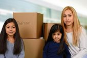 stock photo of daughter  - Mother and her two young daughters packed moving boxes - JPG