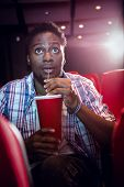 picture of cinema auditorium  - Young man watching a film and drinking soda at the cinema - JPG
