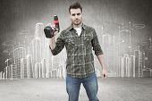 image of hand drill  - Worker holding drill against hand drawn city plan - JPG