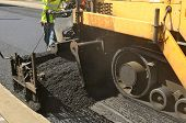 stock photo of paving  - A paver finisher asphalt finisher or paving machine placing a layer of asphalt during a repaving construction project - JPG
