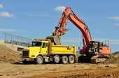 stock photo of dump_truck  - A large track hoe excavator loads a dump truck with dirt and rock on a new commercial construction develoment - JPG