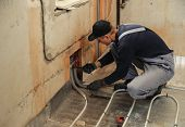 picture of convection  - Man working installer connects the underfloor heating pipes - JPG
