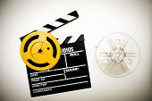 stock photo of mm  - Movie clapper board with super 8 mm film reels yellow and transparent in vintage color effect - JPG