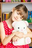 stock photo of stuffed animals  - Girl 6 years with blond hair in a red dress with white polka dots sitting on a chair holding a stuffed toy white bear - JPG