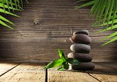 stock photo of stone-therapy  - Spa stones with green leaves on wooden background - JPG