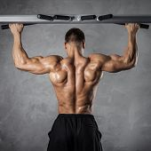 stock photo of pectorals  - Brutal athletic man making pull - JPG