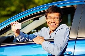 stock photo of driving school  - Happy young man in glasses showing his driving license from open car window - JPG