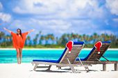 Постер, плакат: Christmas concept: beach loungers with red Santa Hats and beautiful girl during tropical vacation