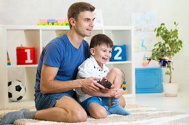 stock photo of helicopters  - Kid boy and father play with  helicopter contolling toy through radio remote control - JPG