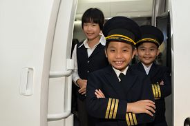 stock photo of cabin crew  - Portrait of little smiling capitan with cabin crew in the airplane - JPG