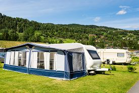 stock photo of caravan  - Modern caravan with caravan tent at campsite in Norway on a sunny summer day - JPG