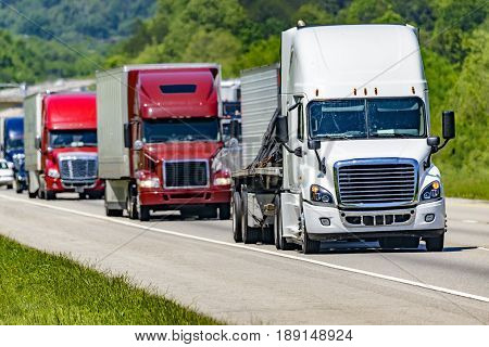 poster of A solid line of eighteen-wheelers barrel down an interstate highway in Tennessee. Heat waves rising from the pavement give a nice shimmering effect to vehicles and trees behind the lead truck.