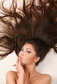 attractive young adult lying on white background with flowing hair