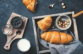 Fresh Croissants With Jam In A Wooden Box, Jar Of Jam, A Glass Of Milk, Nuts Over Dark Concrete Back poster