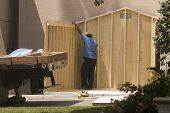 Laborers Building A Shed With Plywood